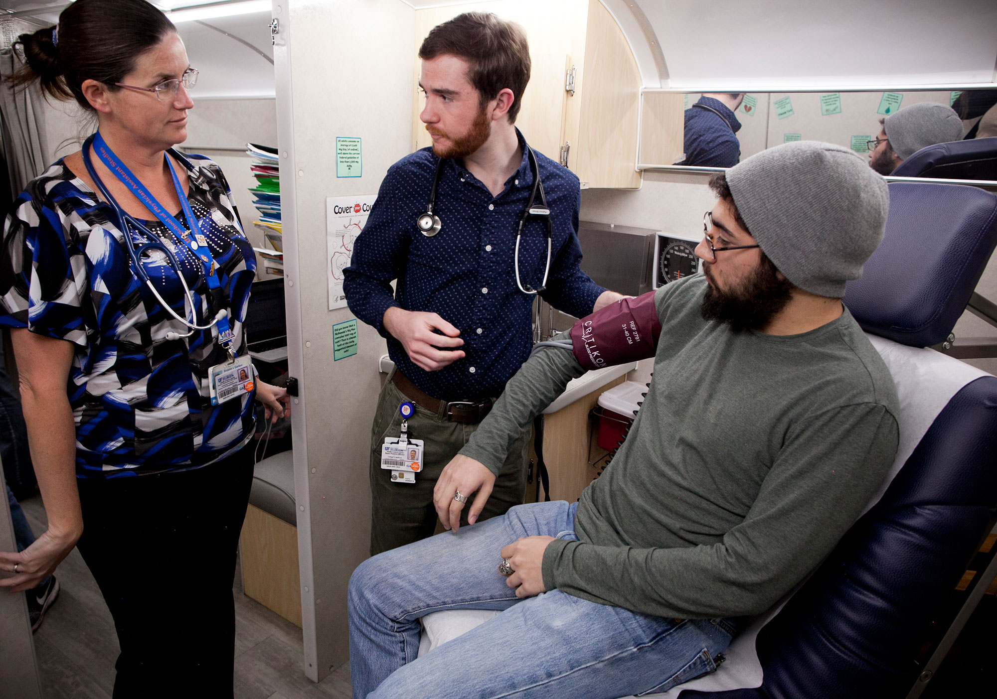 Patrick Bliven (center), aided by a UF attending physician (left), examines a patient in the privacy of UF's Mobile Outreach Clinic.