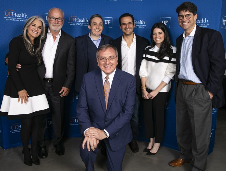 Lauren and Lee Fixel (second and third from right) celebrate the creation of the Norman Fixel Institute for Neurological Diseases, named for Fixel's father, Norman (second to left). Also pictured, from left, are Norman's wife, Susan Fixel, UF Health doctor Michael Okun, UF President Kent Fuchs (kneeling) and UF Health doctor Kelly Foote.