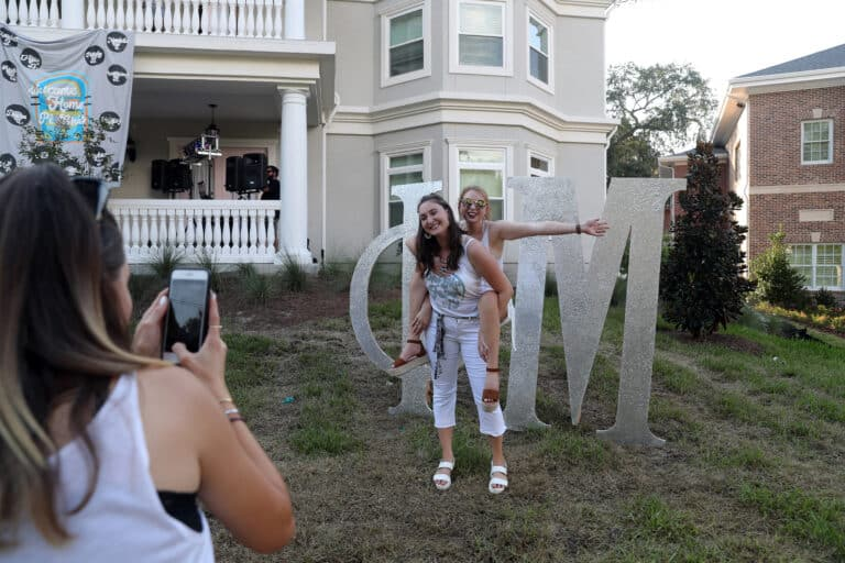 Sorority sister Riley Marshall carries Mariel on the lawn of Phi Mu house.