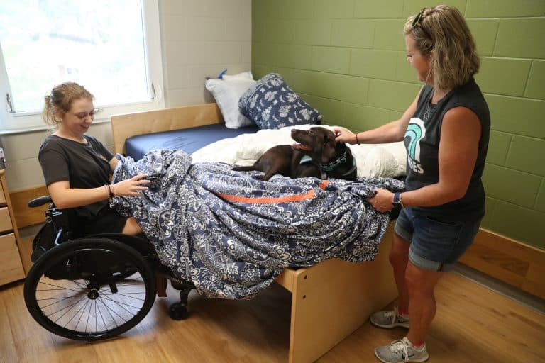 "Service dog Lassie gets in the middle while Mariel and her mother, Jill Olney, make her dorm room bed in Cypress Hall. ""Yes, Lassie, this is your room too,"" says Mariel."