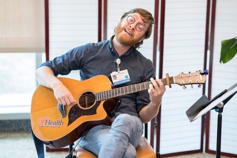 Artists from the UF Arts in Medicine Program have been using their talents to comfort UF Health workers during the pandemic. Here AIM musician-in-residence Michael Claytor strums a nurse's favorite tune during a livestream event.