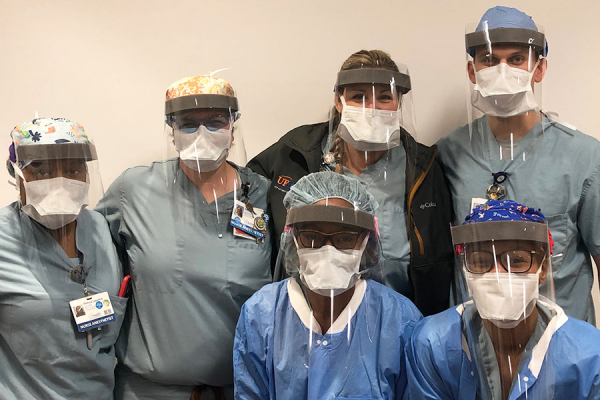 UF Health anesthetists model face shields made by the Powell Family Structures and Materials Laboratory.