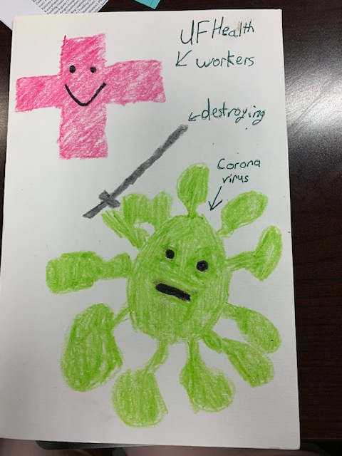 "Hundreds of local children have thanked UF Health workers with handcrafted messages. This child's drawing depicts a smiling pink medical cross (UF Health workers) ""destroying"" a green coronavirus with a sword."