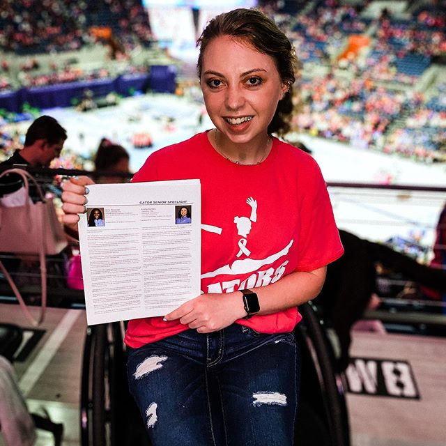 """In 2020, Mariel changed her major from accounting to sports management and began writing stories on Gator athletes for the UF Athletic Association. Here she holds up two profiles she wrote of Gator gymnasts, while viewing a meet at the O'Dome.<br><br>  """"I feel like I've finally found my calling,"""" she wrote on her blog in March."""