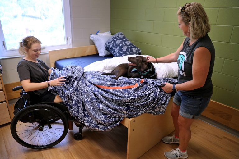 """Mariel returned to UF from Atlanta after nearly two years' absence on August 2, 2019, moving into UF's Cypress Hall residence for students with disabilities. With Lassie looking on, mother Jill Olney helped Mariel settle into her dorm room and did a heroic job of letting go of her daughter for a second time.  """"I'm super happy, super nervous to have her here,"""" said Jill. """"Really, she is ready for this. Plus, I'm only five hours away."""""""