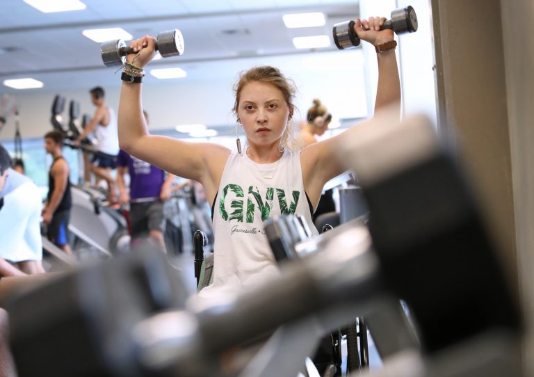 Building upper-body strength has been key to Mariel's rehabilitation and growing independence. Here, she does overhead presses in the Student Rec Center on August 2, 2019.
