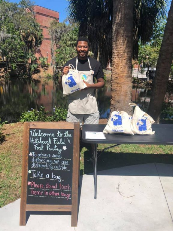 Volunteer Durrell Cobb (BS '20) hands out premade to-go bags of groceries outside the Hitchcock Field & Fork Pantry on April 2.