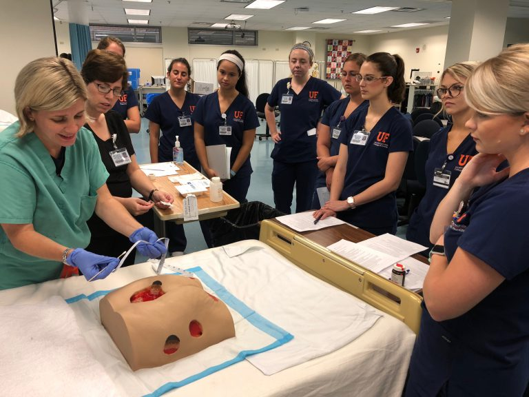 Student nurses gather around a UF instructor as she demonstrates a procedure on a manikin torso that pumps simulated blood.