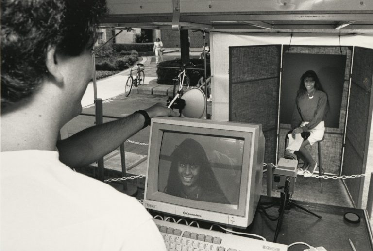 """A computerized UF ID card replaced the old photo ID card in 1990. Here, one of the first UF students to receive a Gator1 ID smiles for the """"video camera"""" in June 1990."""