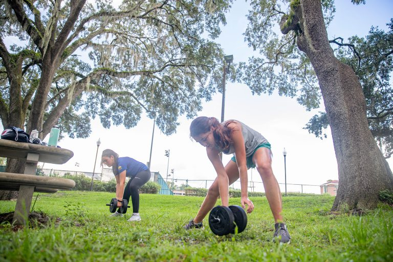 Incoming freshmen Vanessa Sanchez, left, and Catalina Corral exercise on the lawn in the Broward housing area Monday, August 31.