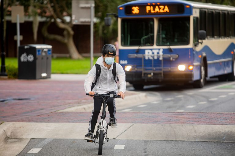 Safety precautions extend to public transport, with mask requirements and stepped up sanitizing aboard busses. A cyclist rides through the University of Florida Campus on the first day of classes on Monday, August 31.