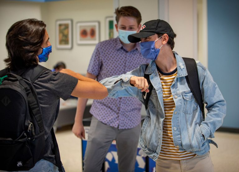 Transfer student Trevor Wayne greets freshman Gian Franco Madonia, left, with an elbow bump, while freshman Graham Corbitt, center, looks on as they meet for the first time for the first day of classes outside the Constans Theatre.