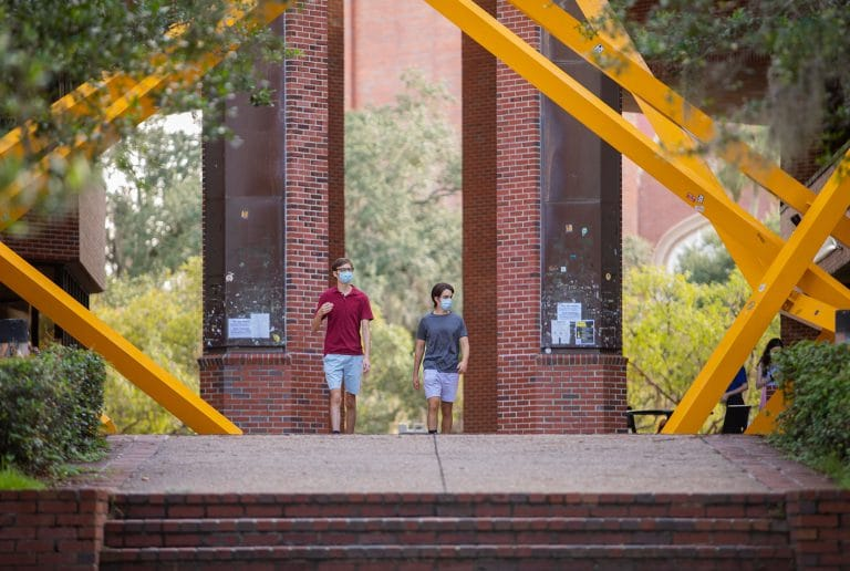 The start of the semester was pushed back by several weeks as UF monitored the pandemic and readied the campus. Incoming freshmen Graham Cope, left, and Alex Klug, right, walk through Turlington Plaza on the first day of classes.
