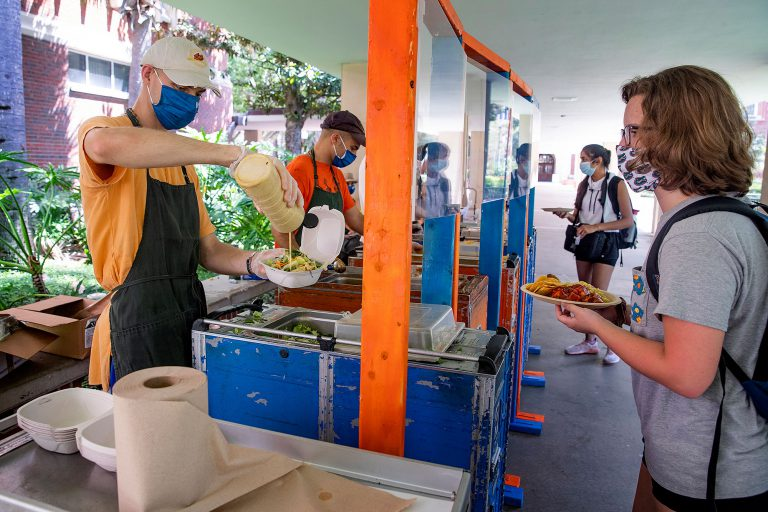 Krishna Lunch had moved to a pick-up and delivery model for much of the summer, returning to campus with safety precautions in place at the start of the semester. Freshman Biology Pre-Professional major Maryanne Bowns, right, walks the new Krishna Lunch line as crew members Madhu Miele, left, and Nate Ball serve from behind protective shielding.