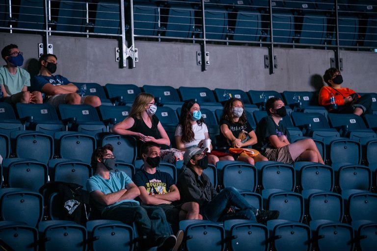 """Students were asked to form """"QuaranTeams"""" – groups who live together or socialize together and follow agreed-upon sets of guidelines for health and safety. Freshmen, sitting with their QuaranTeam, gather to watch movies during The Great Gator Welcome Film Fest at the Stephen C. O'Connell Center on September 4."""