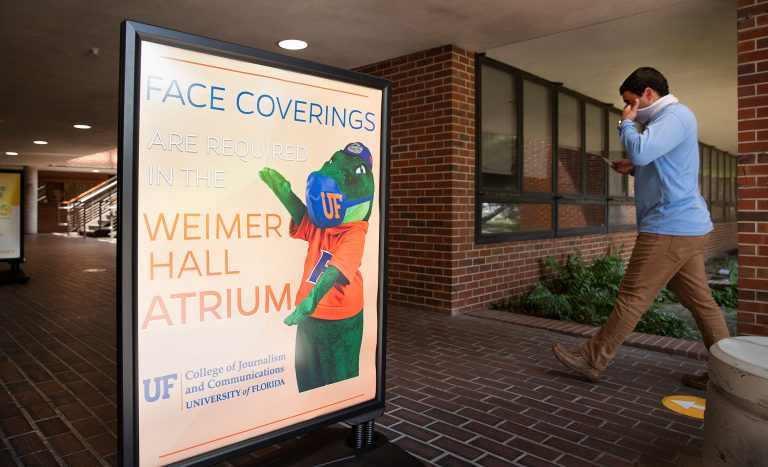 A now-familiar sight: face coverings and reminders to wear them. At the Weimer Hall Atrium at the UF College of Journalism.