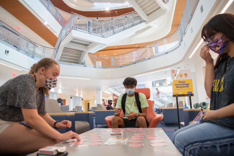 Students socialize with their QuaranTeam at the Reitz Union. From left, sophomore Elizabeth Lantzy, incoming freshman Justin Lanzuela, and senior Ariela Santillan get to know each other while playing a card game called