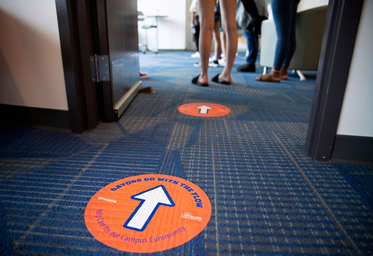 """""""Gators Go With the Flow"""" signs have been placed around campus to ensure as few people as possible are passing each other in narrow spaces."""