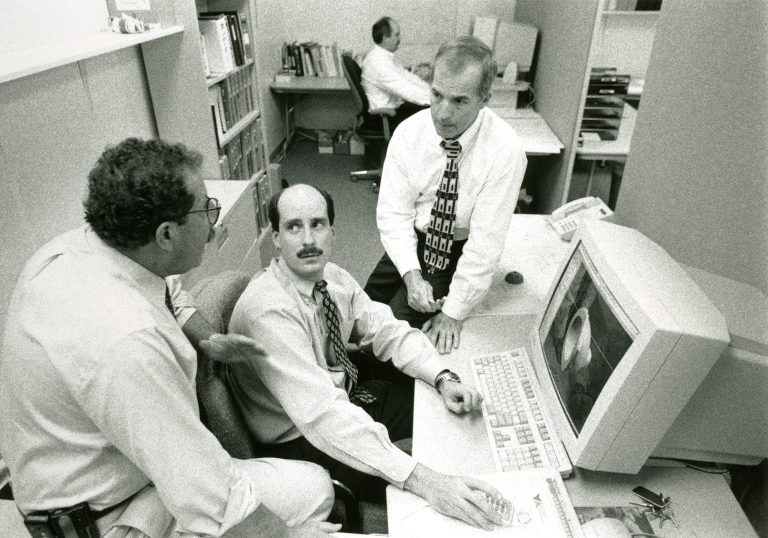 In his company's early days, Dr. Bill Petty (right) and his colleague, biomedical engineer Dr. Gary Miller (left), discuss a computer model of their design of a hip implant device created to solve a previously unmet clinical need.