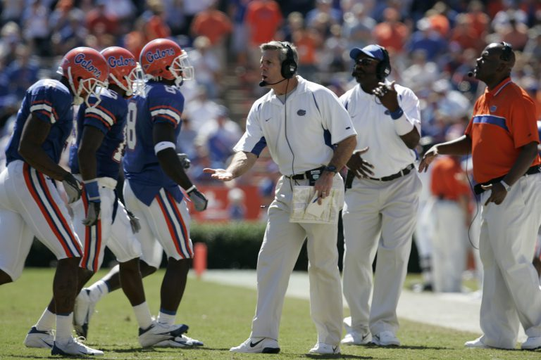 Florida head coach Ron Zook (center) talks with wide receivers No. 8 Chad Jackson (2003-05) and No. 6 Jemalle Cornelius (BSAg '06) and No. 15 defensive back Demetrice Webb (2003-05) on the sidelines. Gators would later learn that was Zook's last season at UF.