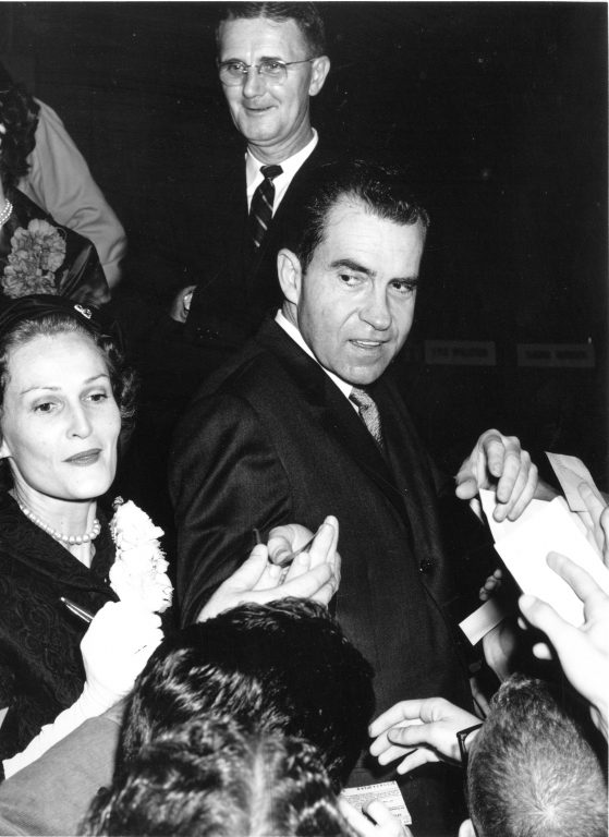 While campaigning for president in 1960, then-Vice President Richard Nixon came with his wife, Pat, to  campus. This photo shows the Nixons signing autographs for an eager crowd of students. Standing in the background is UF President J. Wayne Reitz.