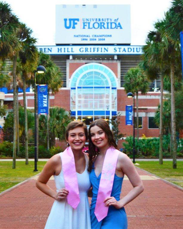"""Norenberg and her Phi Mu """"little sister"""" Jessica Browder (BS '20) pose in front of Ben Hill Griffin Stadium in December 2020. """"Jess came to visit in Gainesville right before my master's graduation,"""" said Norenberg, """"so we took fun graduation pics to make up for our canceled ceremonies in May and my virtual ceremony in December."""" The Greek letters on the pink stole say Phi Mu."""